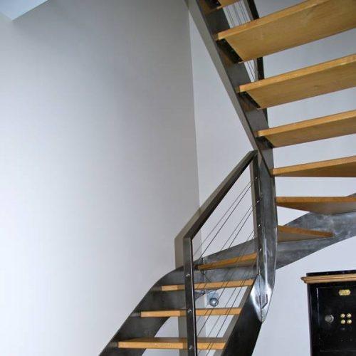 Escalier 2/4 tournant sur mesure, marches en chêne massif et métal brut. Le double limon extérieur épouse parfaitement les cloisons. Les marches sont en chêne massif le métal est resté brut. Créée par Atmos fer, ferronnerie contemporaine à Toulouse.
