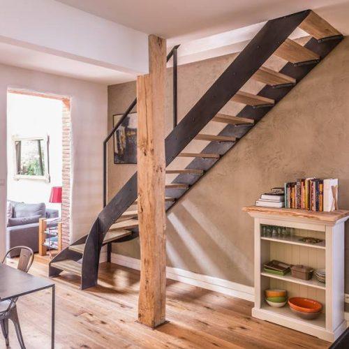 Escalier avec bibliothèque intégrée et un meuble sur mesure formant les premières marches.Escalier avec double limon métal patiné et bois chêne lamellé collé