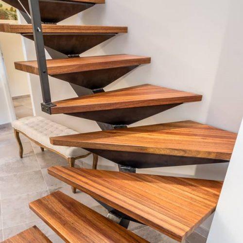 Escalier balancé sur mesure en métal brossées, brunies et patinées. Marches en bois en «Cœur Dehors» . Créée par Atmos fer, ferronnerie contemporaine à Toulouse. Crédit photo Laurent Barranco