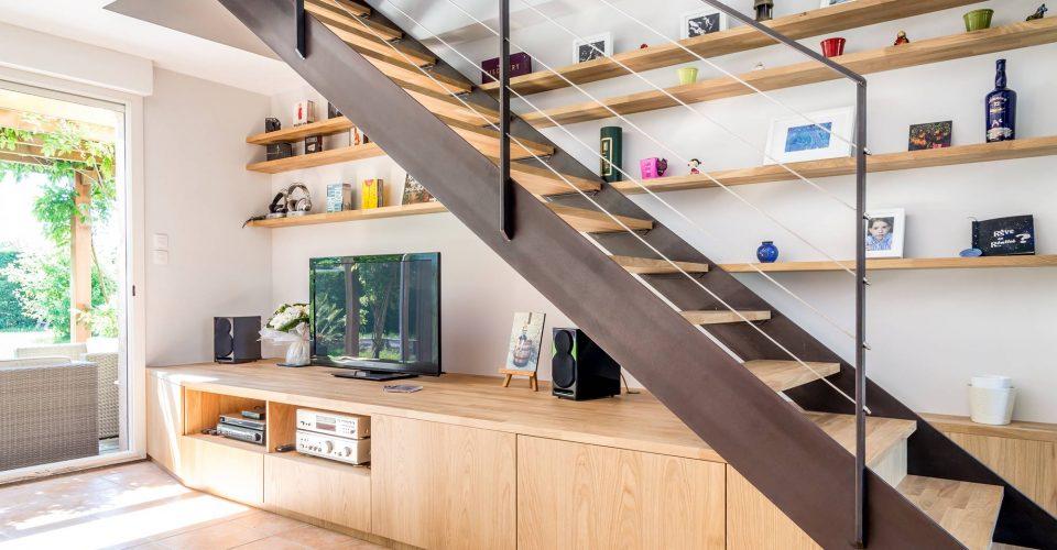 Escalier avec bibliothèque intégrée et un meuble sur mesure formant les premières marches.Escalier avec double limon métal patiné et bois chêne lamellé collé.