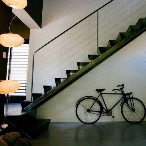 Escalier double limon central en tôle fine d'acier brut, posé sur une poutre en métal. Une rampe légère, avec une main courante en fer plat. Crédit photo : Nathalie Cousin