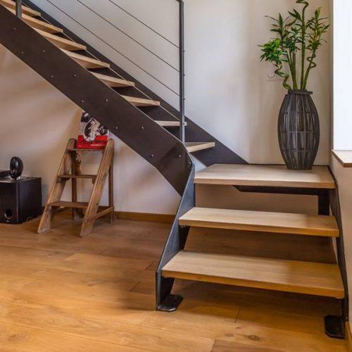 Escalier double limon sur mesure avec un palier intermédiaire, simple, élégant aux proportions subtiles. Rampe en fer plat délicatement poncé pour un toucher agréable et doux. Câbles inox très fin pour donner le plus de transparence possible