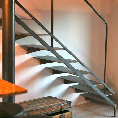 Escalier droit sur mesure double limon en métal brut style indus. Limon intérieur caché dans la cloison. Le limon extérieur ajouré. Rampe au rez de chaussée en tube rond