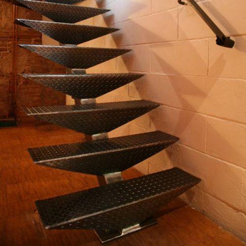 Escalier industriel, acier brut brossé et huilé, Limon central et marches métalliques en tôle larmée avec un pliage sur l'avant qui donne de la rigidité.
