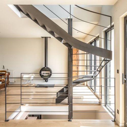 Escalier métal hélicoïdal implémenté sur poteau acier carré autour duquel s'enroule un hélicoïdal sur trémie carrée, qui se termine par une volée droite. Structure (limons et marches) en acier de 10 mm d'épaisseur.