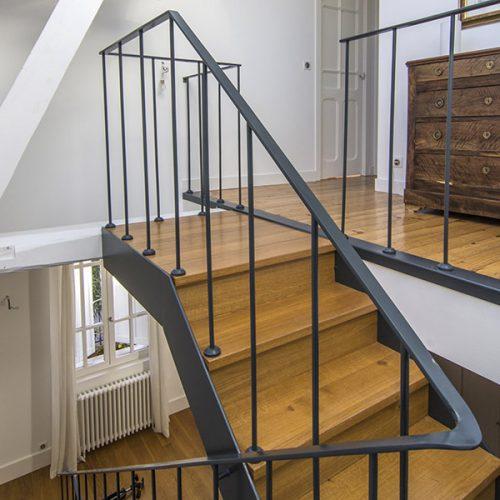 Escalier droit en métal et bois sur mesure, 3 étages dans une maison à Toulouse. Marches et contremarches en chêne massif. Une verrière de toit vient baigner l'ouvrage de lumière.