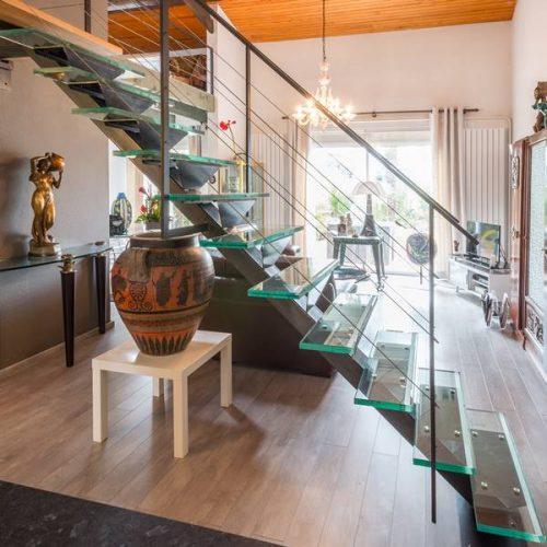 Un escalier métal et verre. Limon central en métal brut ciré, les marches en verres, les câbles en inox. L'escalier métal et verre prendre toute sa place, tout en restant le plus transparent possible. Créée par Atmos fer, ferronnerie contemporaine à Toulouse.