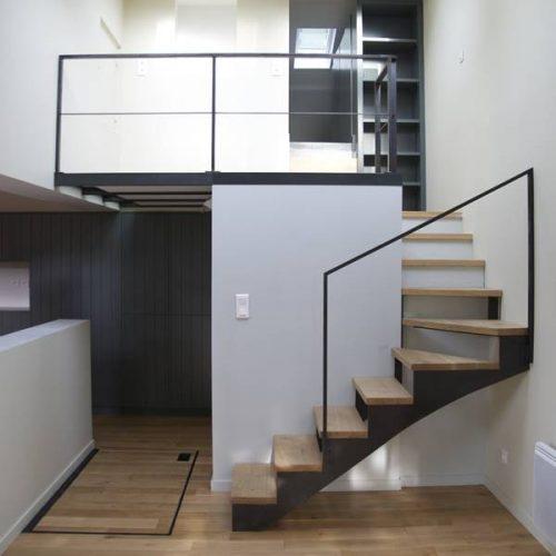 Un escalier pour mezzanine 1/4 tournant rayonnant à doubles limons crémaillères sans contremarches. Les marches en chêne massif. Mezzanine en métal recouverte d'un plancher bois et verre.