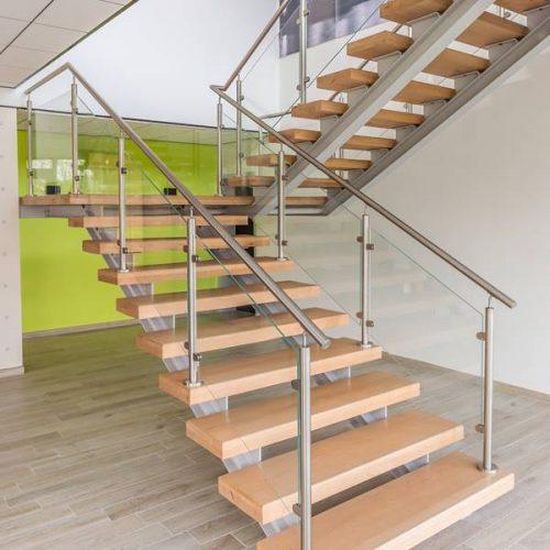 Escalier rampe en verre à voléee et inox brossé. Marches très larges de 1,50 m pour faciliter la circulation. Double limon thermo-laqué gris clair. Gardes corps en inox brossé . Crédit photo Laurent Barranco