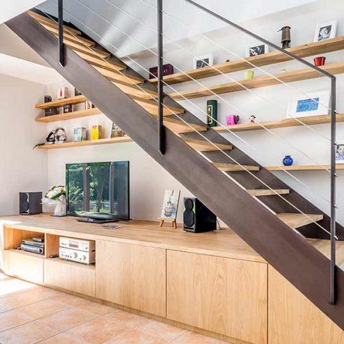Escalier avec bibliothèque intégrée et un meuble sur mesure formant les premières marches. Escalier avec double limon métal patiné et bois chêne lamellé collé.