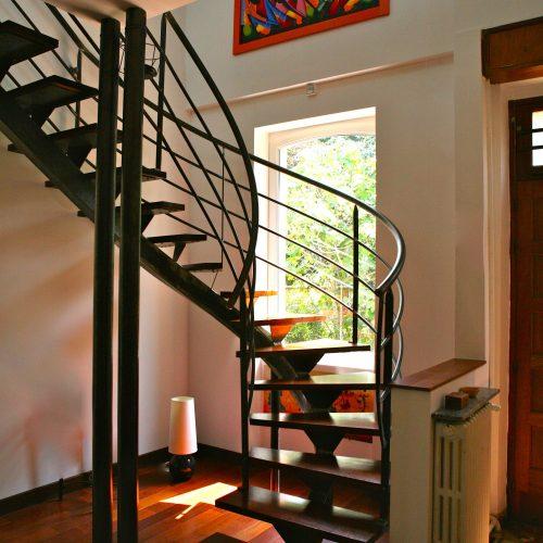 Escalier 2/4 tournant balancé avec limon central, supports de marches en métal, marches en bois exotique