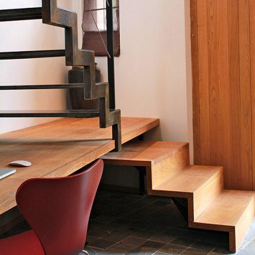 Escalier avec bureau métal et bois à crémaillère. Création sur-mesure pour aligner le plan de travail du bureau avec la hauteur de la marche. Créé par Atmos Fer, ferronnerie contemporaine à Toulouse.