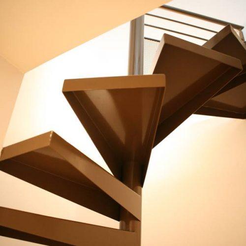 Escalier colimaçon sur mesure en métal plié en tôle peinte. Garde corps de l'étage en tube rond avec une partie basse en tôle ajourée