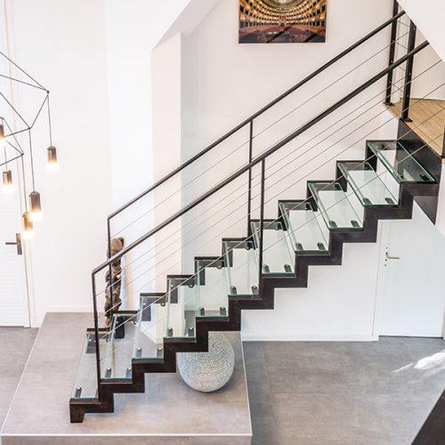 Escalier droit métal et verre sur mesure devient sculpture et donne tout son caractère au hall d'entrée. Marches en verre feuilleté trempé alliant transparence et grande résistance.